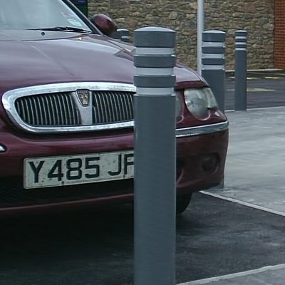 grey polymer bollard in front of a car
