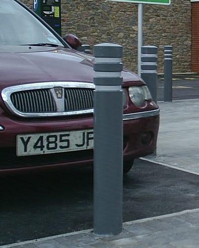 grey polymer bollard in front of a car