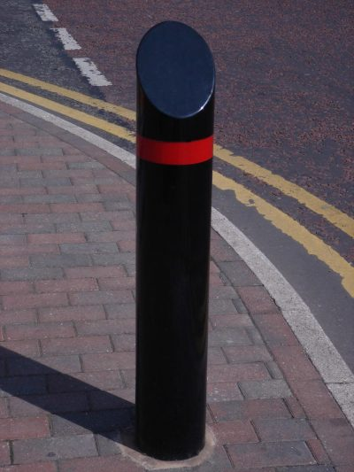 black polyester powder coated bollard on a street with a red band
