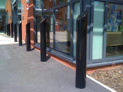 sloped top mildsteel bollard powder coated black infront of shops