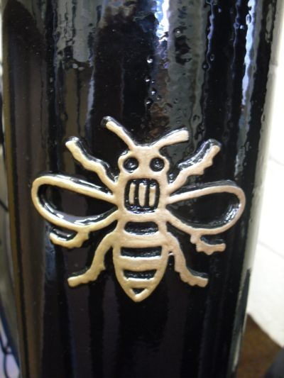 close up of the manchester bee highlited in gold on a black polymer bollard