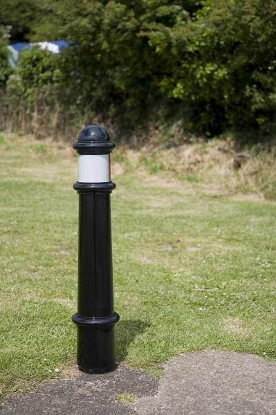 black polymer bollard on grass with a white band