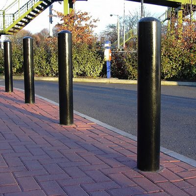 black polyester powder coated mild steel bollard on a pavement protecting a building