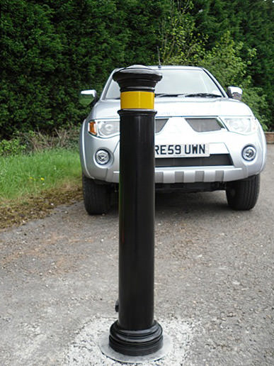 Manchester polyurethane bollard in front of a parked car