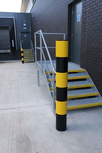 black and yellow bollard in front of a warehouse