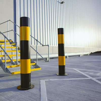 black and yellow banded mild steel high visibility bollards protecting a building