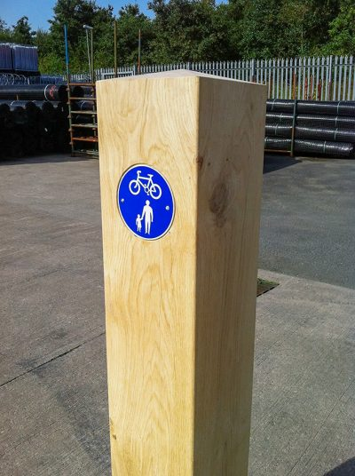blue signage on an oak timber bollard