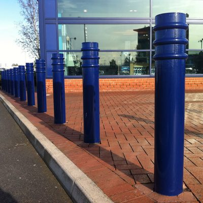 powder coated blue mild steel bollards in front of a shop