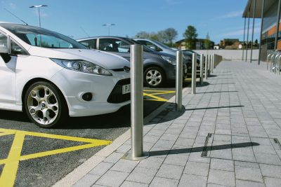 stainless steel bollards in a line in front of parked cars on a sunny day