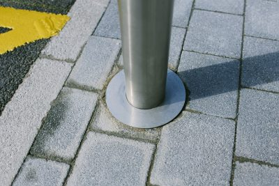baseplate detail of a stainless steel bollard on a blockwork pavement
