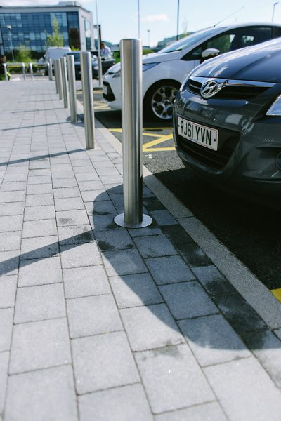 baseplated stainless steel bollards sitting infront of parked cars