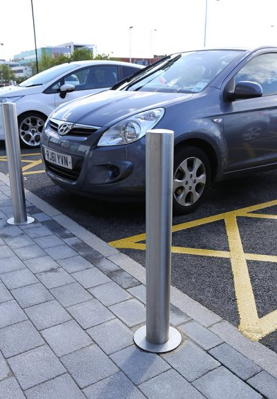 close up of stainless steel bollard with cars in the background