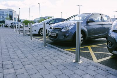 line of Tella stainless steel bollard in front of parked cars in a shopping car park