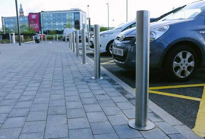 line of stainless steel bollards in front of parked cars