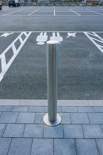 stainless bollard in front of a car parking space