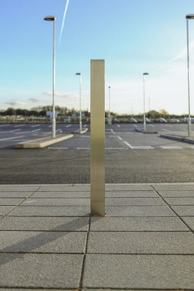single shot of a stainless steel bollard infront of a car park
