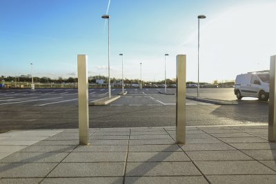 low down view of square stainless steel bollard that avery reflective