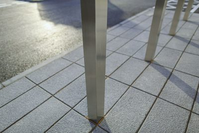 close up of square stainless steel bollards in front of a car park