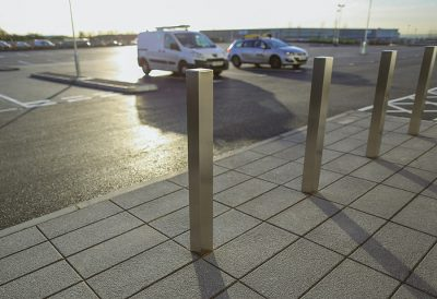Square stainless steel bollards on a pavement