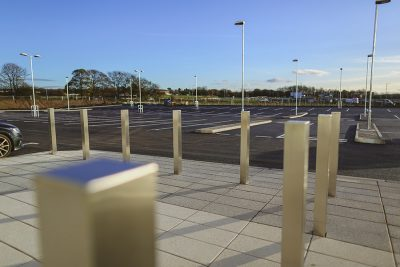 square stainless steel bollard infront of a car park
