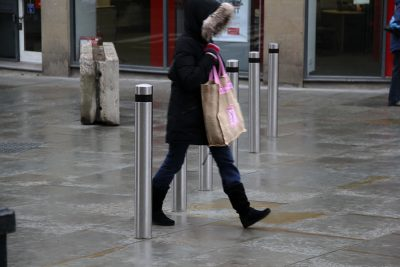 woman walking between a row of stainless steel bollard in a high street