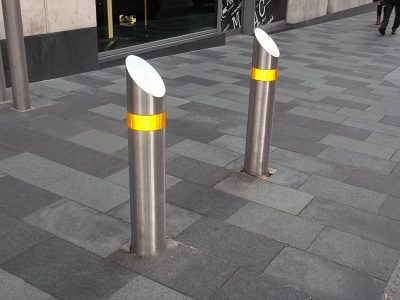 stainless steel bollard in a sreet with yellow rflective banding