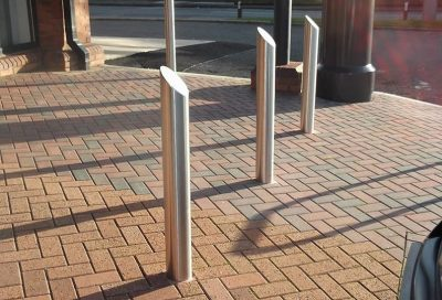 row of stainless steel bollard with sloped top on a street