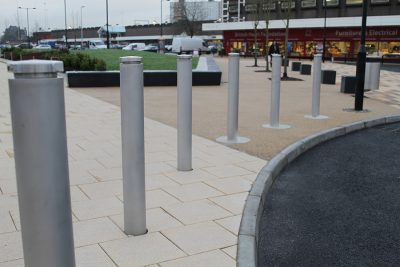 row of stainless steel bollard in front of a shopping center