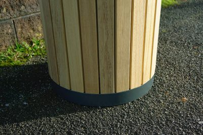 a litter bin outside on a path made from timber and steel